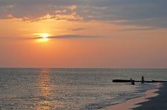 Дети в силуэте играя на пляже Стоковое Фото
