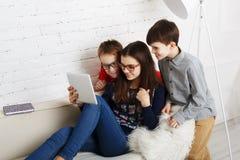 Дети в стеклах с устройствами, наркоманией компьютера Стоковая Фотография
