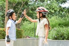 Дети в шлемах высоко--fiving в парке стоковые фотографии rf