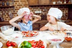 Дети в шляпах шеф-повара имея потеху пока делающ пиццу Стоковое Фото