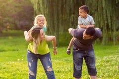дети давая родителей piggyback езда к стоковое фото