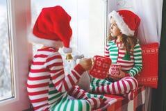 Дети девушка и мальчик грустны на утре рождества окном стоковое фото