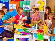 Дети делают что-то из покрашенной бумаги стоковое изображение