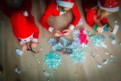 Дети делая снежинки из бумаги, ремесла рождества стоковое фото rf