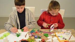 Дети делая украшение на праздники, ремесла и игрушки, рождественская елка и другое Акварели картины Взгляд сверху Workpl художест сток-видео