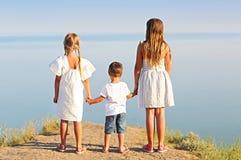Дети держа руки морем стоковые фотографии rf
