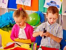Дети девушки и мальчика отрезали бумагу на таблице в детском саде Стоковые Изображения RF
