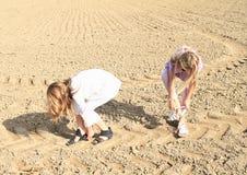 Дети - девушки кладя на ботинки на поле Стоковые Фотографии RF
