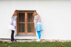 Дети - девушки наблюдая в окно Стоковые Изображения RF