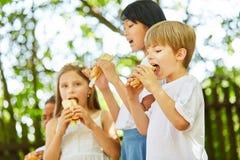 Дети едят очень вкусные крены багета стоковые фото