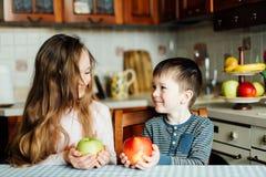 Дети едят яблока в кухне на утре Сестра и брат держат яблоко в их руках Стоковое Изображение RF