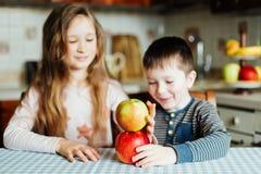 Дети едят яблока и имеют потеху в кухне на утре Стоковое фото RF