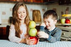 Дети едят яблока и имеют потеху в кухне на утре Стоковые Изображения