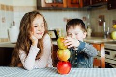 Дети едят яблока и имеют потеху в кухне на утре Стоковая Фотография