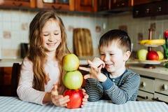 Дети едят яблока и имеют потеху в кухне на утре Стоковое Изображение RF