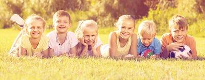 Дети лежа на зеленой траве Стоковые Изображения RF