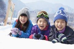 Дети лежа на снеге Стоковая Фотография