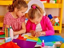 Дети держа покрашенную бумагу на таблице в детском саде Стоковая Фотография RF