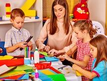 Дети держа покрашенную бумагу на таблице в детском саде Стоковое фото RF