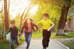 Дети держа руки и ход в парке стоковые фото