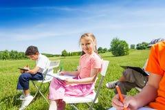 Дети держа эскиз-доски и сидят на стульях Стоковая Фотография