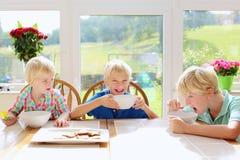 Дети есть дома в кухне Стоковое Изображение