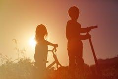 Дети ехать велосипед и самокат на заходе солнца Стоковые Фотографии RF