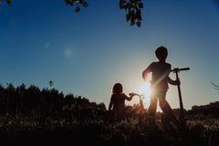 Дети ехать велосипед и самокат на заходе солнца Стоковые Изображения RF