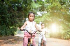 Дети ехать велосипеды внешние Стоковые Изображения