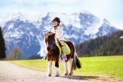 Дети ехать пони Ребенок на лошади в горах Альпов стоковые изображения