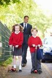 Дети ехать самокаты на их пути к школе с отцом стоковое изображение rf