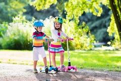 Дети ехать самокат в парке лета Стоковая Фотография