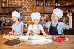 Дети делая тесто пиццы и подготавливая ингридиенты пиццы Стоковое Фото