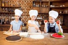 Дети делая тесто пиццы и подготавливая ингридиенты пиццы Стоковое Изображение