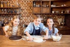 Дети делая тесто пиццы на деревянной столешнице Стоковая Фотография
