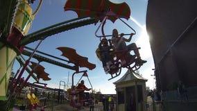Дети едут на веселой езде в парке атракционов Промежуток времени видеоматериал