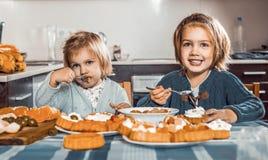 Дети едят торты на кухне Стоковые Изображения