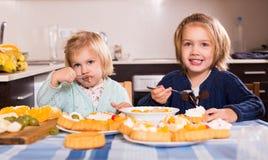 Дети едят торты на кухне Стоковая Фотография RF