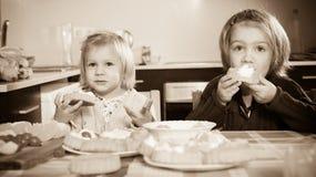 Дети едят торты на кухне Стоковое Изображение