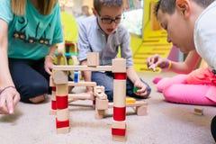 Дети женского воспитателя уча для того чтобы построить цепь поезда Стоковые Фото