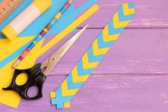 Дети завертывают закладку в бумагу на деревянной предпосылке с космосом экземпляра для текста Простые бумажные ремесла дома или ш Стоковые Изображения