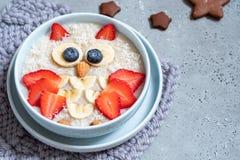 Дети завтракают каша овсяной каши с ягодами и гайками стоковые изображения rf