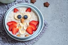 Дети завтракают каша овсяной каши с ягодами и гайками стоковые фото