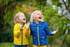 Дети играют в дожде осени Ребенок на дождливый день стоковые изображения rf