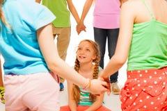 Дети играют игру, девушку сидят в круге Стоковое Изображение