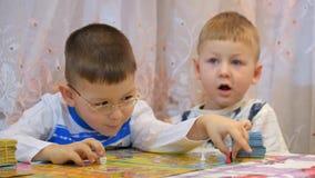 Дети играют настольные игры на таблице с семьей видеоматериал