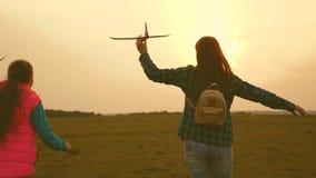Дети играют самолет игрушки Счастливые сестры девушки, который побежали с самолетом игрушки на заходе солнца на поле Концепция сч сток-видео