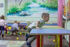 Дети играя активные игры в детском саде стоковые фото