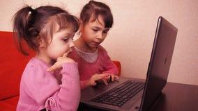 Дети играя в компьтер-книжке 2 маленькой девочки напечатаны на компьтер-книжке 2 сестры сидя на оранжевом кресле смотря подол видеоматериал
