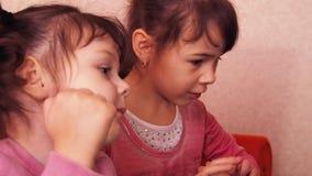 Дети играя в компьтер-книжке 2 маленькой девочки напечатаны на компьтер-книжке 2 сестры сидя на оранжевом кресле смотря подол акции видеоматериалы